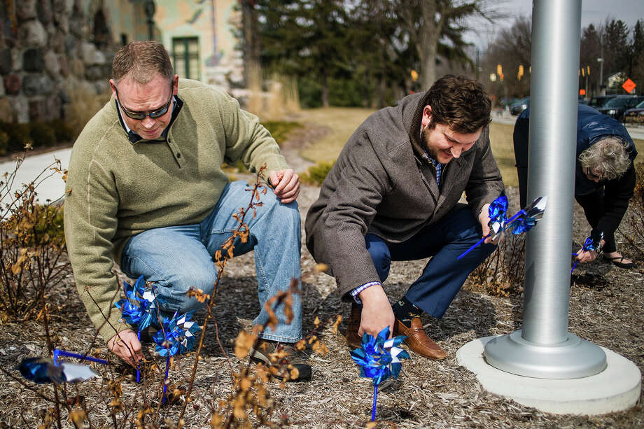 Midland residents Jon Pohl, left, and Blain Anderson, right, place pinwheels in the ground during Safe and Sound Child Advocacy Center's annual pinwheel ceremony on Tuesday, April 2, 2019 in front of the Midland County Courthouse. (Katy Kildee/kkildee@mdn.net) Photo: (Katy Kildee/kkildee@mdn.net)