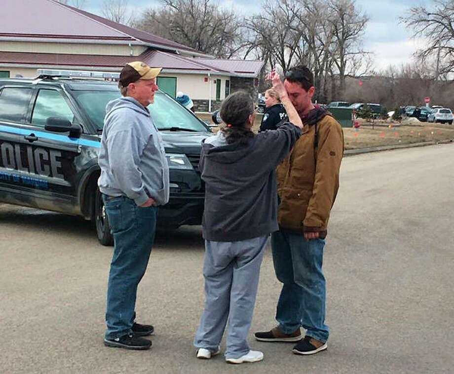 "Gina Kessel, center, comforts her son Mitchell outside of RJR Maintenance and Management, a property management company, Monday, April 1, 2019, Mandan, N.D. Authorities say police responding to a medical call at the North Dakota business have found ""several"" bodies. The Mandan Police Department issued a three-sentence news release confirming that officers had found ""several people who were deceased inside"" the business in the city of about 22,000 just across the Missouri River west of Bismarck. Photo: AP Photo/Blake Nicholson"