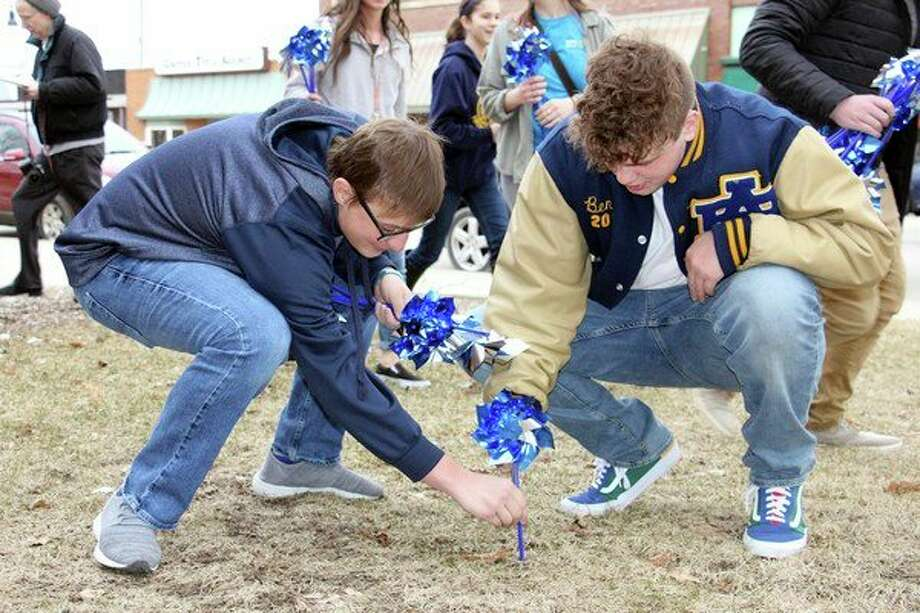 Bad Axe High School students and other members of the community joined the Huron County CA/N Council on Tuesday to plant a garden of pinwheels on the Huron County Building lawn. The efforts are to raise awareness for the prevention of abuse and neglect for Huron County's littlest residents. Together, students and community members planted more than 500 pinwheels. For more photos of the event, see Page 2A. (Bradley Massman/Huron Daily Tribune)