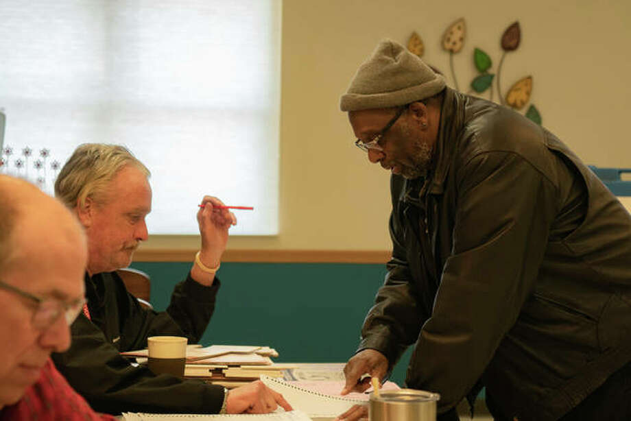 Retired teacher Jame Pete Evans gets his ballot from an election judge before heading over to a voting booth Tuesday at Main Street Community Center in Edwardsville. Photo: Breanna Booker | The Intelligencer