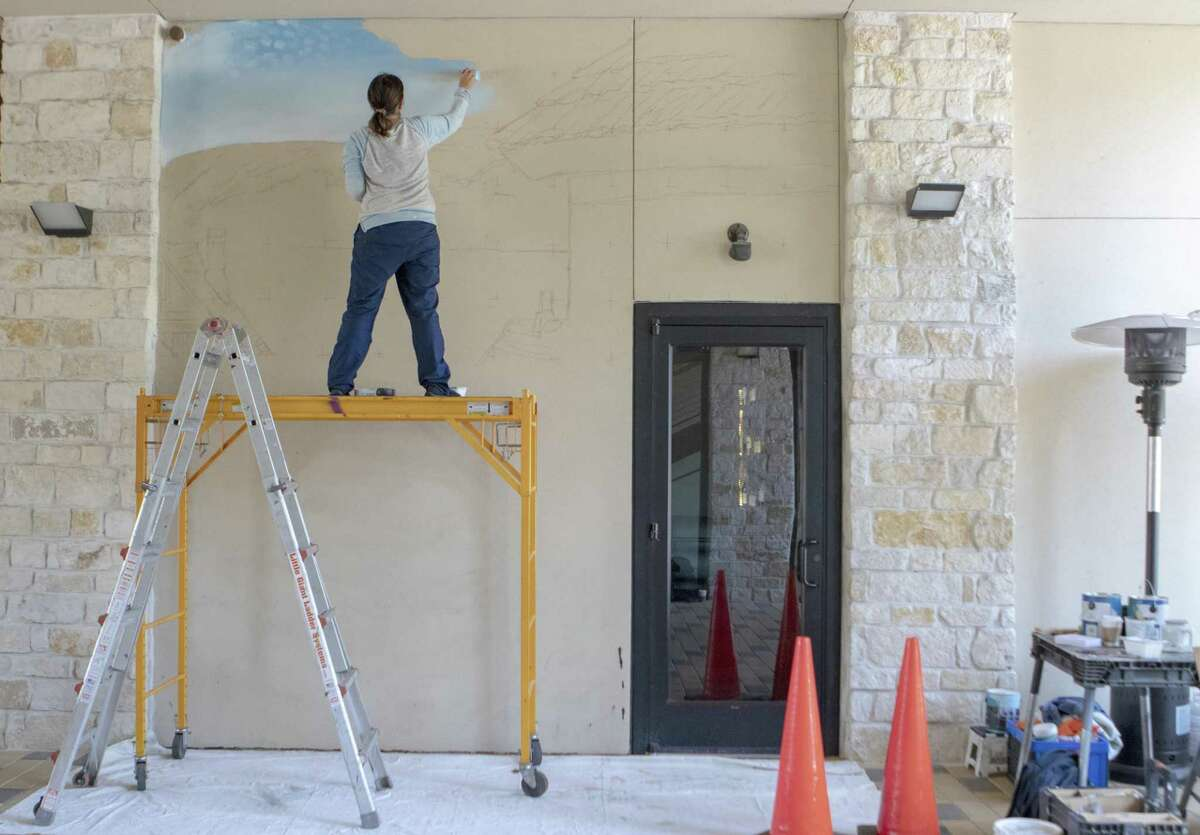 Artist Anat Ronen paints the sky for a mural Tuesday, April 2, 2019 at Creekside Park Village Green in The Woodlands. Ronen began painting the mural Tuesday and is expected to be finished Thursday.