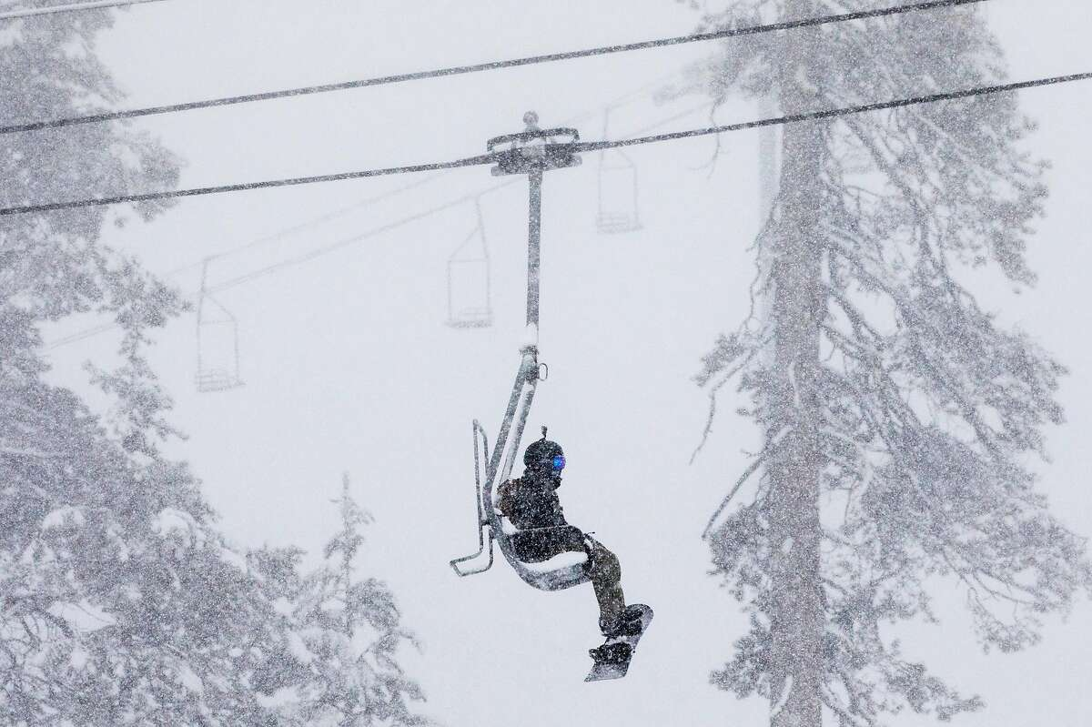 A snowboarder rides the ski lift up the mountain during a moderate snowfall at Sierra-at-Tahoe Resort in Twin Bridges, Calif. Tuesday, April 2, 2019.