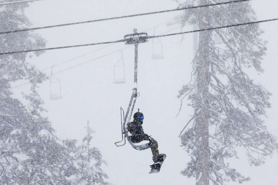 A snowboarder rides the ski lift up the mountain during a moderate snowfall at Sierra-at-Tahoe Resort in Twin Bridges, Calif. Tuesday, April 2, 2019. Photo: Jessica Christian / The Chronicle