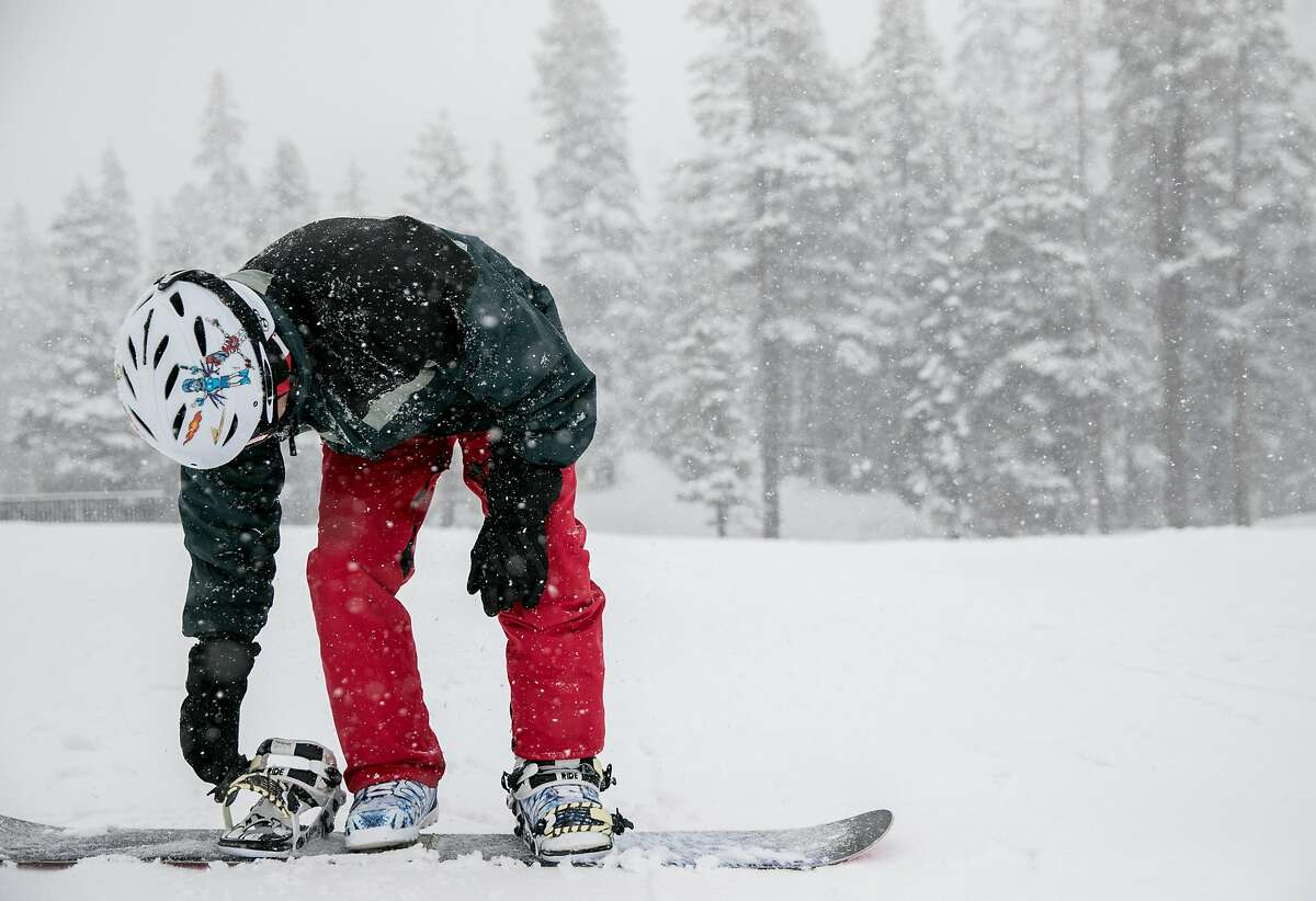 A snowboarder buckles his boots in before enjoying the slopes during a moderate snowfall at Sierra-at-Tahoe Resort in Twin Bridges, Calif. Tuesday, April 2, 2019.