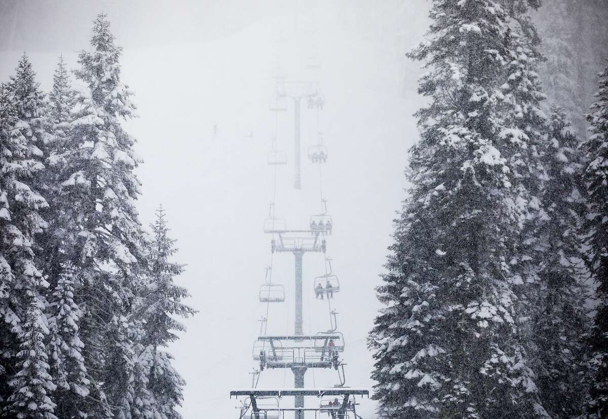 Skiiers and snowboarders ride a ski lift up the mountain during a moderate snowfall at Sierra-at-Tahoe Resort in Twin Bridges, Calif. Tuesday, April 2, 2019.