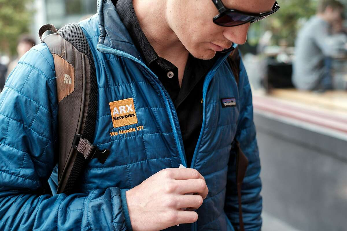 Nick Shmel, an IT worker for ARX Networks, wears a Patagonia jacket that is branded with his company's logo, in San Francisco, Calif., on Tuesday April 2, 2019. In an effort to force a more eco minded approach for tech and finance companies, Patagonia announced that it will stop facilitating corporate branding on it's products for company's that do not reach B corporation status.