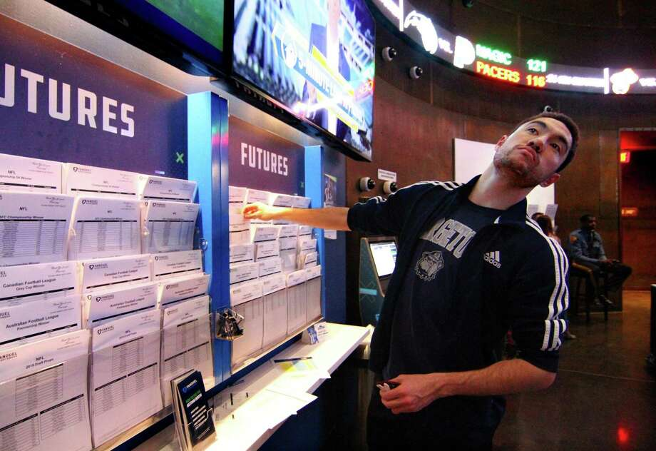 While checking the futures out, Michael Brandon, of Stamford, pauses to see the Texas Tech NCAA basketball game, during a day at Fan Dual sportsbook at the Meadowlands in East Rutherford, New Jersey on March 29, 2019. Connecticut is considering legalizing sports betting, leaning toward a New Jersey model where people can bet in person at casinos and racetracks, as well as online. Photo: Christian Abraham / Hearst Connecticut Media / Connecticut Post