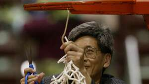 Seattle Pacific University coach Jeff Hironaka cuts down the net after his team beat Western Washington University at Royal Brougham Pavilion in Seattle to move on to the NCAA elite 8 on Monday March 13, 2006.  Joshua Trujillo / Seattle Post-Intelligencer