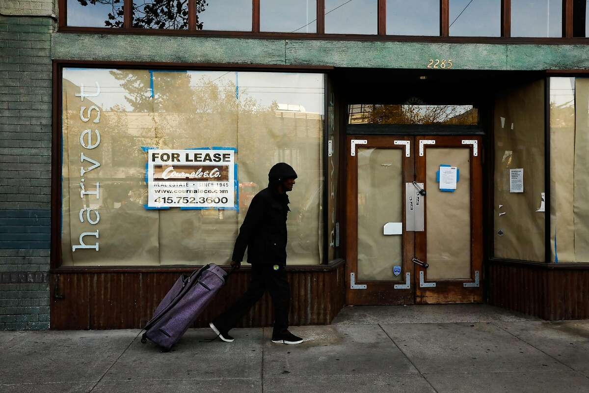 A person passes by a shuttered storefront on Market Street in the Castro neighborhood in San Francisco, California, on Monday, Oct. 29, 2018.