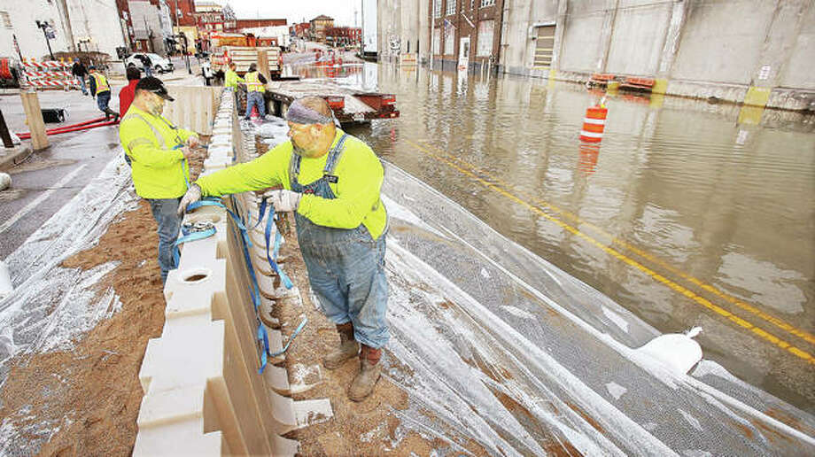 Alton Public Works employees set up the city's modular flood wall late Monday to avoid working in the water on Tuesday, when they had planned to erect the wall. The river was forecast to crest overnight Tuesday into Wednesday morning. Photo: John Badman | The Telegraph