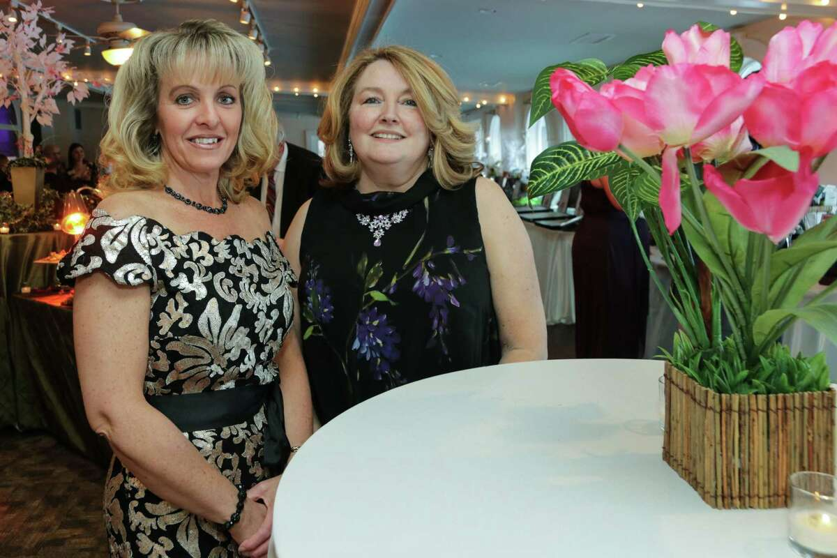 Executive Director Jeannine Garab and Director of Development Susan Kaczsynki pose in front of decorations that queued the Enchanted Garden theme of the 31st Confections in Chocolate Gala for the Epilepsy Foundation of Northeastern New York. (Kennedy Lawson)