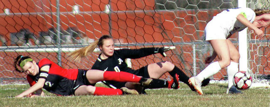 Alton's Megan Zini, left, and goalie Addison Miller keep an eye on the ball from ground level as Colllinsville's Mikaila Chrisman, right, tries to get around on it for a shot during Tuesday's Southwestern Conference game at Alton High. The teams battled to a scoreless tie through regulation before Alton posted a 2-1 overtime victory. Photo: Pete Hayes | The Telegraph