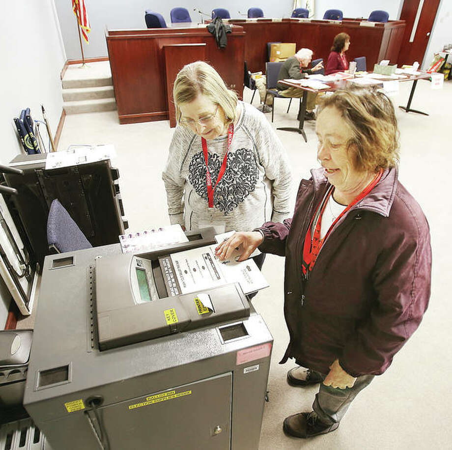 Election judge Lillian Phipps, left, watches as fellow judge Bonnie McClain, of Wood River, feeds her ballot into the tabulation machine Tuesday morning at Wood River Precinct 3, which voted at Wood River City Hall. McClain took advantage of the peace and quiet to cast her vote while waiting. By 9 a.m. only five people had cast ballots in the precinct by that time. Photo: John Badman | The Telegraph