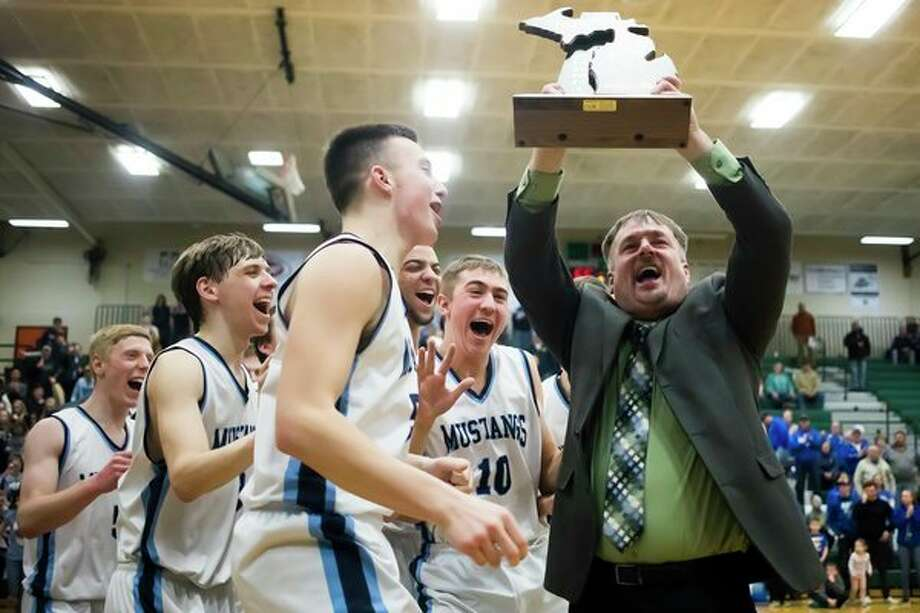 Meridian head coach Mitch Bohn celebrates after the Mustangs' 65-44 Division 3 regional finals victory over Oscoda on Thursday at Houghton Lake High School. (Katy Kildee/kkildee@mdn.net)