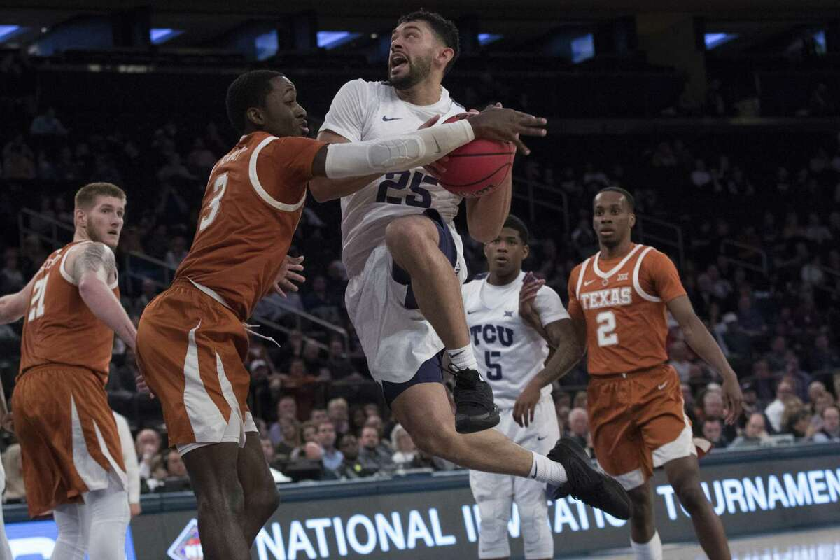 TCU guard Alex Robinson goes airborne on his drive only to encounter UT guard Courtney Ramey at Madison Square Garden.