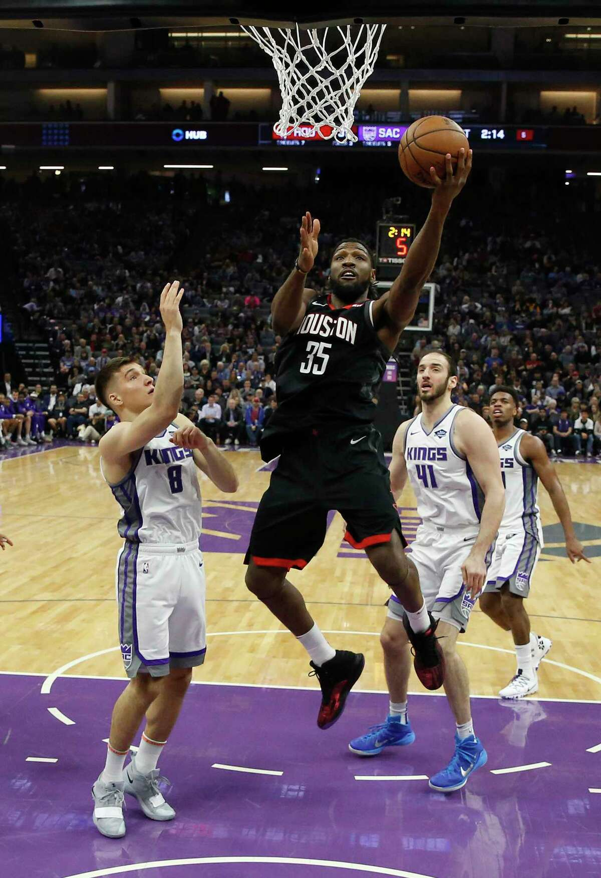 Houston Rockets forward Kenneth Faried, center, goes to the basket against Sacramento Kings guard Bogdan Bogdanovic, left, as Kings center Kosta Koufos, third from left, looks on during the first quarter of an NBA basketball game, Tuesday, April 2, 2019, in Sacramento, Calif.(AP Photo/Rich Pedroncelli)