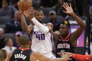 Sacramento Kings forward Harrison Barnes, center, passes between Houston Rockets' Eric Gordon, left, and Clint Capela, right, during the first quarter of an NBA basketball game, Tuesday, April 2, 2019, in Sacramento, Calif.(AP Photo/Rich Pedroncelli)