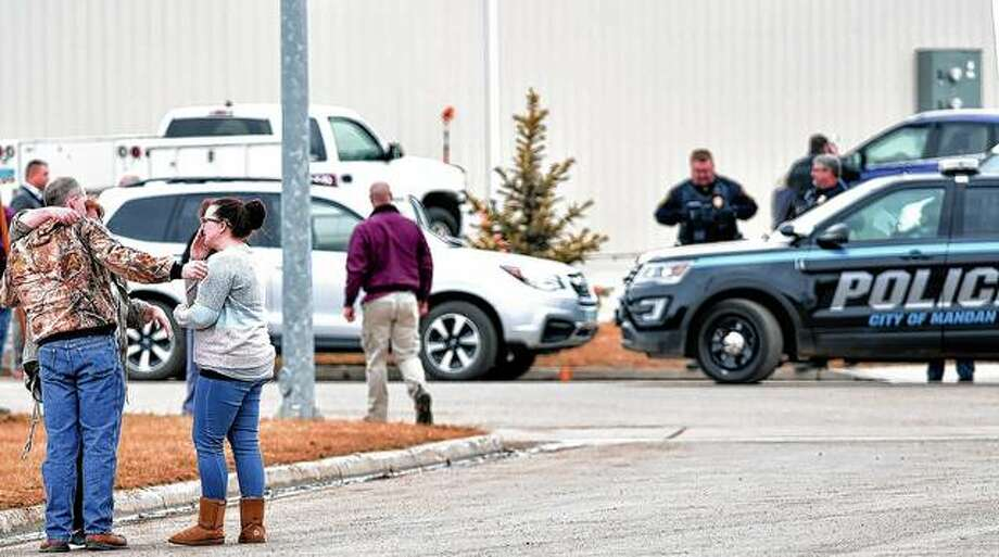 Family and friends console each other at the scene near the south side of the RJR Maintenance and Management building in Mandan, North Dakota.