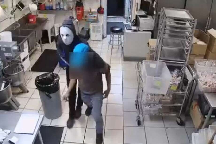 Store surveillance video shows the armed suspect had wrapped his or her arm around a store employee and almost dragged them to a back area of the building before fleeing with a box of cash in hand. Photo: Houston Police Department/Crime Stoppers