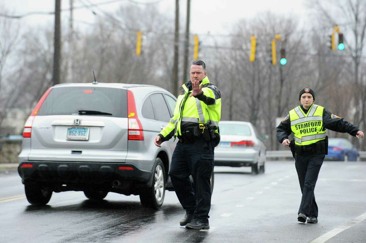 Stamford police officers Melanie Miscioscia, right, helps flag down distracted drivers on Tuesday, April 4, 2017. Miscioscia and her partner, Abhishek Herekar, recently transported a sick 11-month-old baby to Stamford Hospital after the parents reported he was not breathing. The child was discovered to have the flu and is recovering.