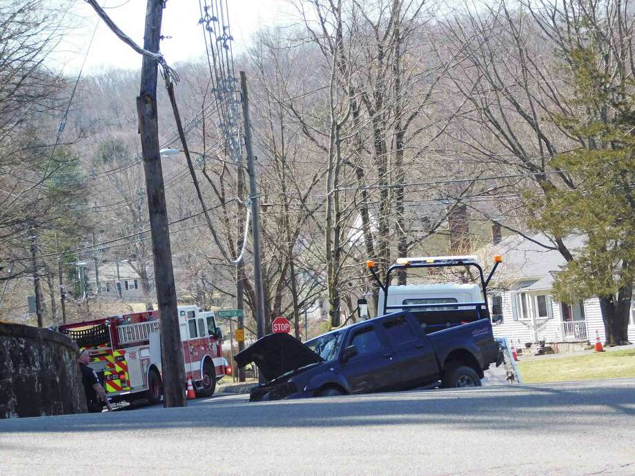 A pickup truck is lifted onto the back of a tow truck after crashing into a pole on Southern Boulevard on April 3, 2019. Photo: Kendra Baker / Hearst Connecticut Media