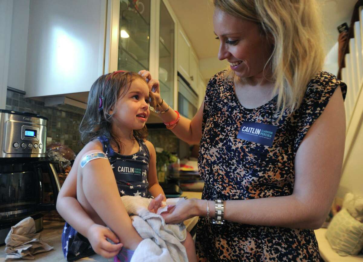 Candidate for Fairfield state representative Caitlin Clarkson Pereira comforts her daughter, Parker, 3, in her Fairfield home after Parker skinned her knee while going door to door in Fairfield, Conn. on Wednesday, August 22, 2018. Clarkson Pereira was denied her request to the State Elections Enforcement Commission to use her campaign funds to pay for child care.