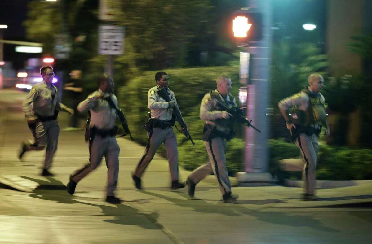 FILE - In this Oct. 1, 2017, file photo, police run for cover at the scene of a shooting near the Mandalay Bay resort and casino on the Las Vegas Strip in Las Vegas. In a report released Tuesday, Jan. 29, 2019, the FBI concluded its investigation into the deadliest mass shooting in modern U.S. history without determining a motive. After nearly 16 months, the agency says it can't determine why gunman Stephen Paddock killed 58 people and injured nearly 900 others in October 2017. (AP Photo/John Locher, File)