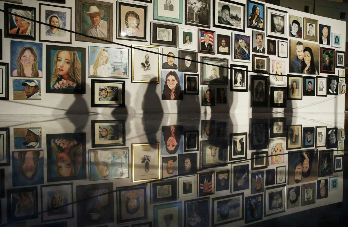 FILE - In this Monday, Sept. 17, 2018, file photo, people's shadows fall upon portraits of victims of the mass shooting in Las Vegas. Portraits of the 58 people killed in last year's mass shooting in Las Vegas went on display Monday after artists from around the world donated their time to memorialize the victims. (AP Photo/John Locher, File)