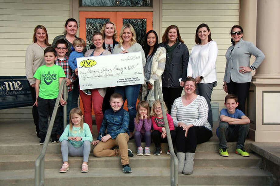 Edwardsville Children's Museum staff, surrounded by children, accept a $1,500 donation from Junior Service Club of Edwardsville/Glen Carbon for four new window decals. The decals not only cut light and heat entering the first floor, but highlight the museum, making it stand out for new visitors. Pictured with their children are: Maci Bohlman, Judy Blaskie, Sarah Dawson, Lisa Grote, Amber Koester, Karen Marcus, Kelly Ruehl, Abby Schwent, Janice Stone and Andrea Walsh. Photo: Charles Bolinger | The Intelligencer