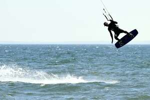 Taking advantage of the warm weather and high winds, a man catches air while kite surfing at Walnut Beach in Milford on April 3, 2019.