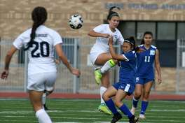 Kingwood senior Catherine Childs, center, controls the ball for a header against C.E. King defender Nubia Sanchez, right, during the first half of their Region III-6A Bi-District Playoff matchup at Crenshaw Memorial Stadium in Houston on March 29, 2019.