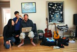"""(Names cq'd from left to right) Yuki, 47, Kosei, 10, and Kyle Retzik, 43, browse their laptop in their home in San Francisco, California on Saturday, July 7, 2018. The family is experiencing a difficult situation after their original landlord was foreclosed and an LLC purchased the property. The company has nearly doubled their rent after realizing they couldn't evict the Retzik's without just cause. """"It's definitely stressful. These aren't like people who are like a family who bought the house and now they're going to move in here,"""" said Kyle Retzik. """"This is like a nameless LLC that is not even from San Francisco -- they're from LA-- that are essentially real estate speculators. They want to buy and flip this house instead of having a family live here."""" The Retzik's have managed to pay the rent increase for the last two months. """"It's not easy and it makes me nervous,"""" said Yuki Retzik."""
