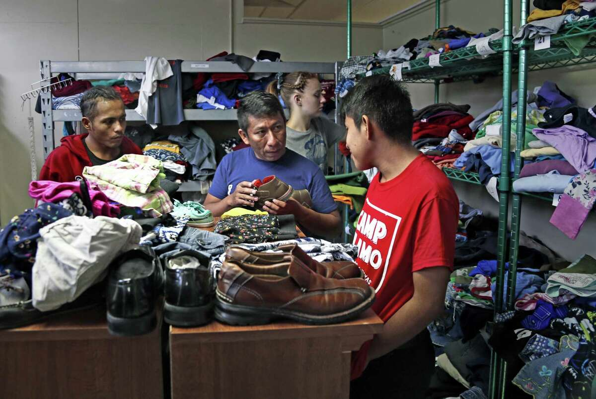 Recently released from border patrol custody, migrants look for clothes at the Guadalupe Community Center, provided by Catholic Charities who is helping to process the large increase in migrants being dropped off in San Antonio daily.