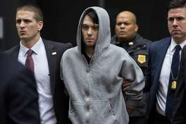 FILE - In this Dec. 17, 2015, file photo, Martin Shkreli, the former hedge fund manager under fire for buying a pharmaceutical company and ratcheting up the price of a life-saving drug, is escorted by law enforcement agents in New York, after being taken into custody following a securities probe. Pharmaceutical honcho Shkreli has been banished to solitary confinement amid allegations he was running his drug company from federal prison using a contraband smartphone, a person familiar with the matter told The Associated Press. (AP Photo/Craig Ruttle, File)