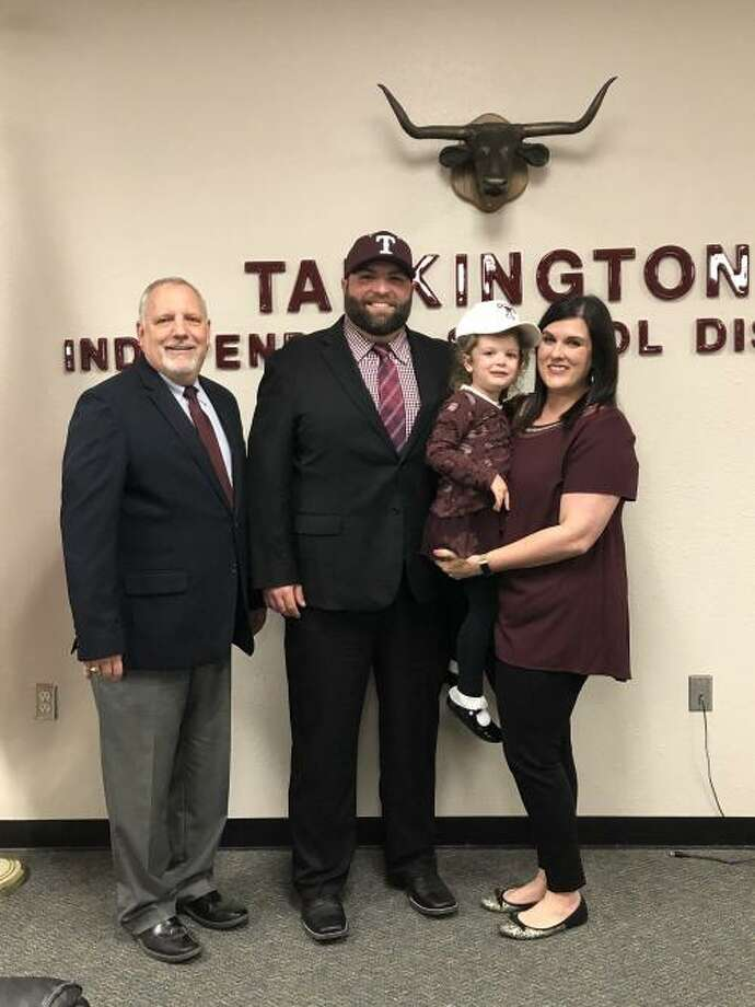 Former Memorial offensive coordinator Zach Bass (middle) poses for a picture following his hiring on Tuesday night to be the head football coach and athletic director at Tarkington High School. Photo: Photo Provided By Tarkington ISD.