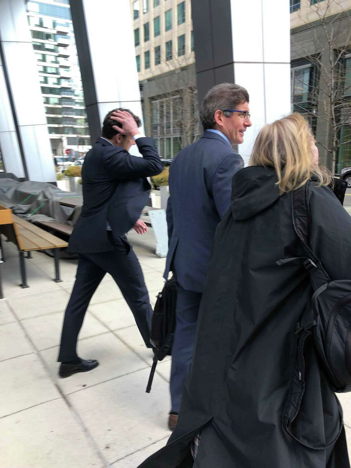 Reporters chase after Gordon Caplan, a Greenwich lawyer, as he leaves the courthouse in Boston on Wednesday with his attorney, Joshua Levy, a formal federal prosecutor in Massachusetts.