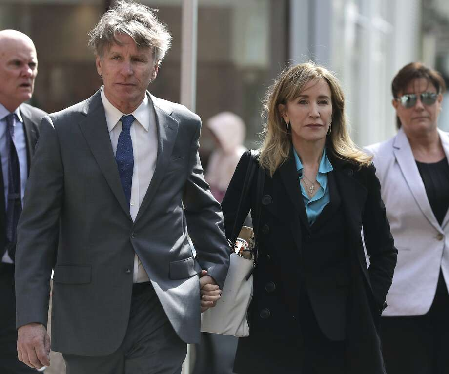 Actress Felicity Huffman arrives holding hands with her brother Moore Huffman Jr., left, at federal court in Boston on Wednesday, April 3, 2019, to face charges in a nationwide college admissions bribery scandal. (AP Photo/Charles Krupa) Photo: Charles Krupa / Associated Press