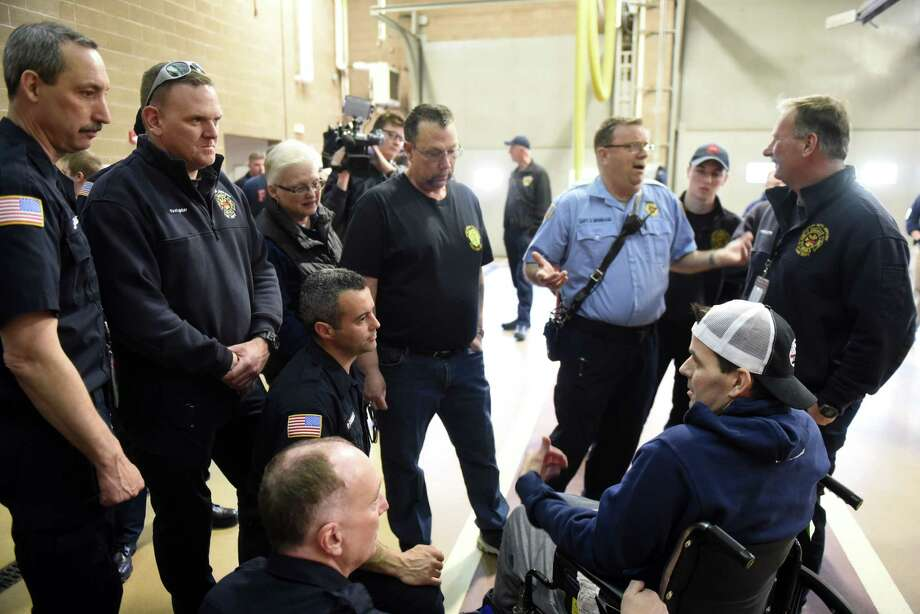 Albany International Airport firefighter Josh Woodward, right, enjoys some time with co-workers after his wife, Chelsea, took him on a surprise visit to the firehouse on Wednesday, April 3, 2019, in Colonie, N.Y. Woodward nearly died after an infection turned septic. (Will Waldron/Times Union) Photo: Will Waldron, Albany Times Union / 40046581A