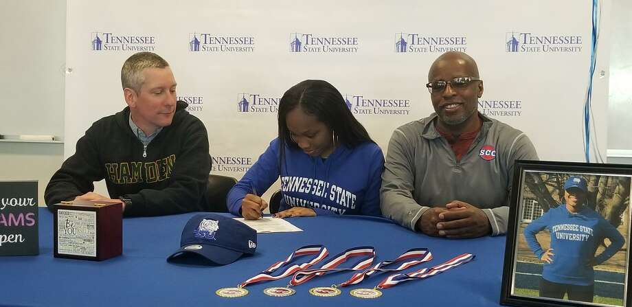 Hamden High senior Tori Roberts, center, signing her national letter of intent to compete in track and field at Tennessee State next season. She is flanked by Hamden outdoor coach Bryce Lindamood, left, and mentor Bob Davis, a longtime track coach in the area. Photo: Joe Morelli / Hearst Connecticut Media