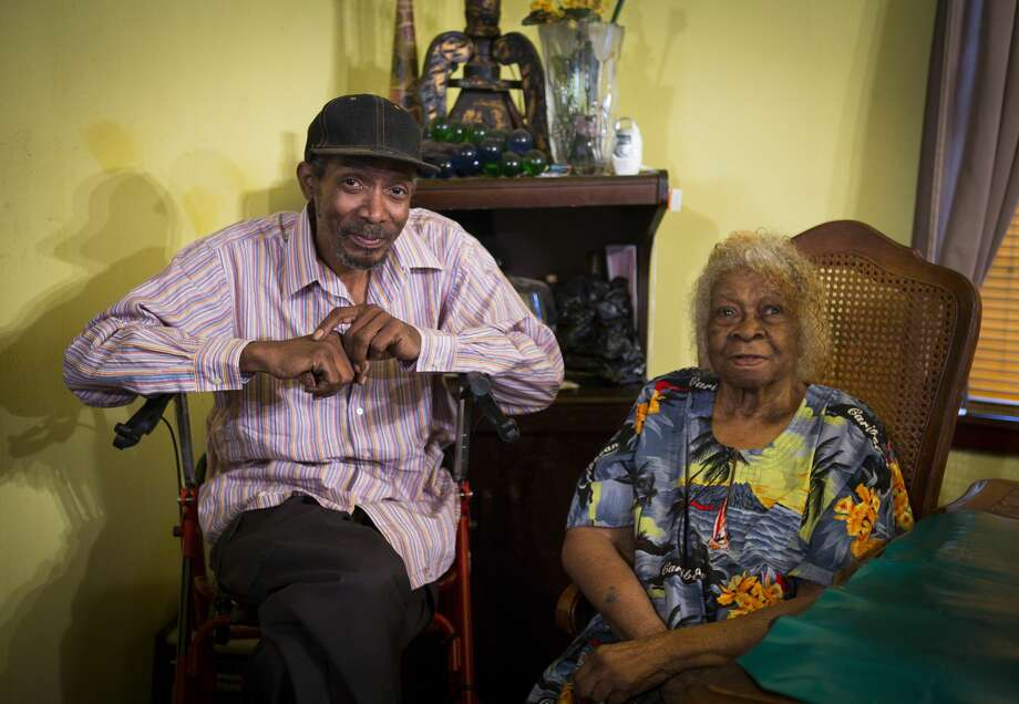 Malberth Moses sits with his elderly mother in their Harvey-damaged home. Photo: Mark Mulligan/Staff Photographer