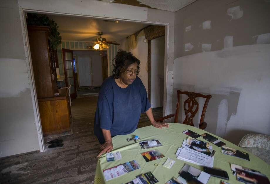 Annie Green looks at photos and business cards from contractors and relief organizations that she has collected since the storm. Photo: Mark Mulligan/Staff Photographer