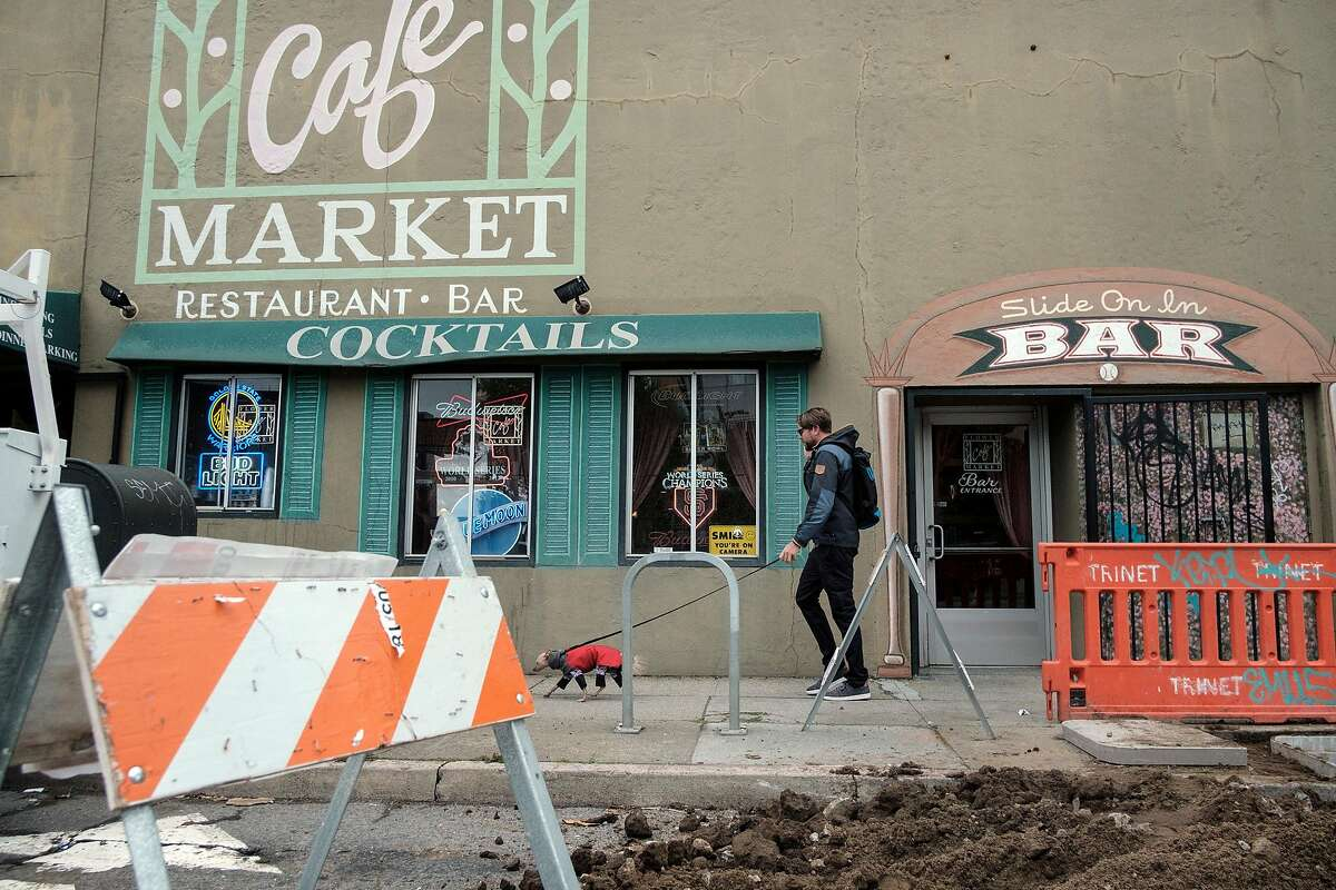 A person walks past construction outside of Bechelli's Flower Market Cafe in the San Francisco Flower Mart in San Francisco, Calif., on Wednesday April 3, 2019.