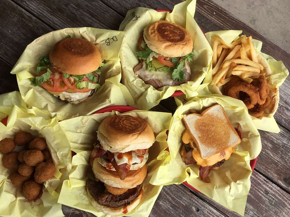 A lineup of burgers at sides at Chunky's Burgers & More includes (clockwise from top left): the classic double cheeseburger, Monterrey Burger, fries and onion rings, Texas Kicker, Hickory Burger, Tejas BBQ Burger and fried mushrooms.