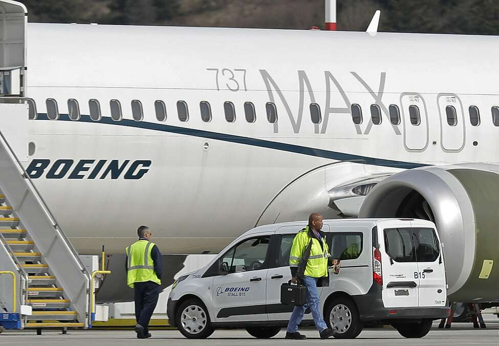 FILE - In this March 14, 2019, file photo, workers walk next to a Boeing 737 MAX 8 airplane parked at Boeing Field, in Seattle. A published report says pilots of an Ethiopian airliner that crashed followed Boeing's emergency steps for dealing with a sudden nose-down turn but couldn't regain control. (AP Photo/Ted S. Warren, File)