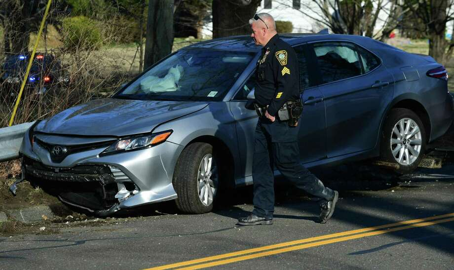 Norwalk police respond to an accident scene on Rowayton Ave. where the driver lost control of the Toyota Camry he was driving after a vehicle pursuit by police Wednesday, April 3, 2019, in Norwalk, Conn. Three individuals were in the car during a suspected narcotics transaction that led to the pursuit. The suspects engaged officers in a foot pursuit following the crash. One suspect had to be extracted from a muddy river bed. Two are being held in custody and one was released. Photo: Erik Trautmann / Hearst Connecticut Media / Norwalk Hour