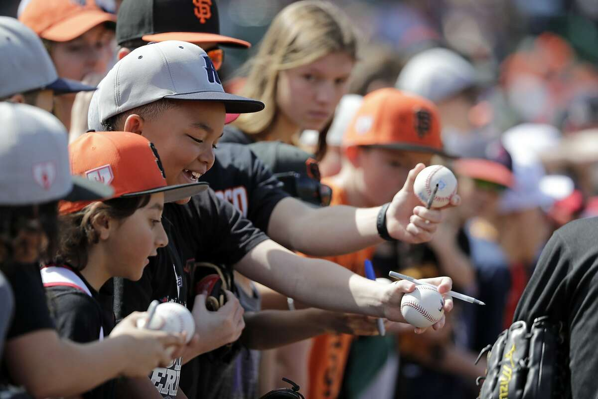 Fans hold out baseballs as they try to get autographs from players before a spring training baseball game between the Los Angeles Angels and San Francisco Giants Friday, March 15, 2019, in Phoenix. (AP Photo/Elaine Thompson)