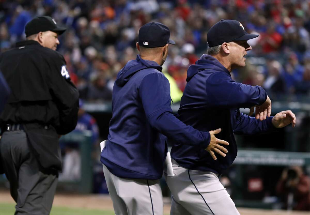 Umpire Ron Kulpa walks away after ejecting Houston Astros manager AJ Hinch, right, who is escorted off the field by bench coach Joe Espada during the second inning of the team's baseball game against the Texas Rangers in Arlington, Texas, Wednesday, April 3, 2019. (AP Photo/Tony Gutierrez)