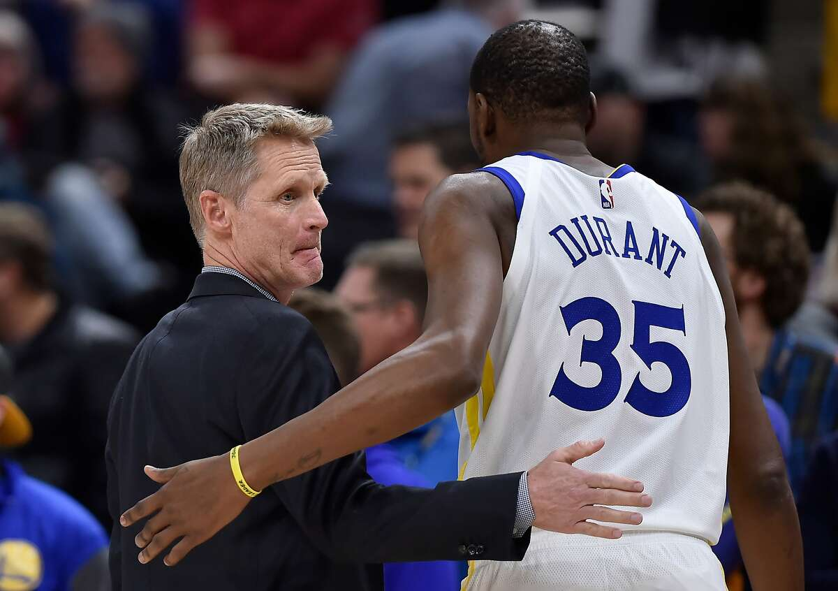 Head coach Steve Kerr of the Golden State Warriors talks with his Kevin Durant in the first half of a NBA game against the Utah Jazz at Vivint Smart Home Arena on Dec. 19, 2018, in Salt Lake City, Utah.