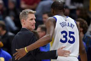 SALT LAKE CITY, UT - DECEMBER 19: Head coach Steve Kerr of the Golden State Warriors talks with his player Kevin Durant #35 in the first half of a NBA game against the Utah Jazz at Vivint Smart Home Arena on December 19, 2018 in Salt Lake City, Utah. NOTE