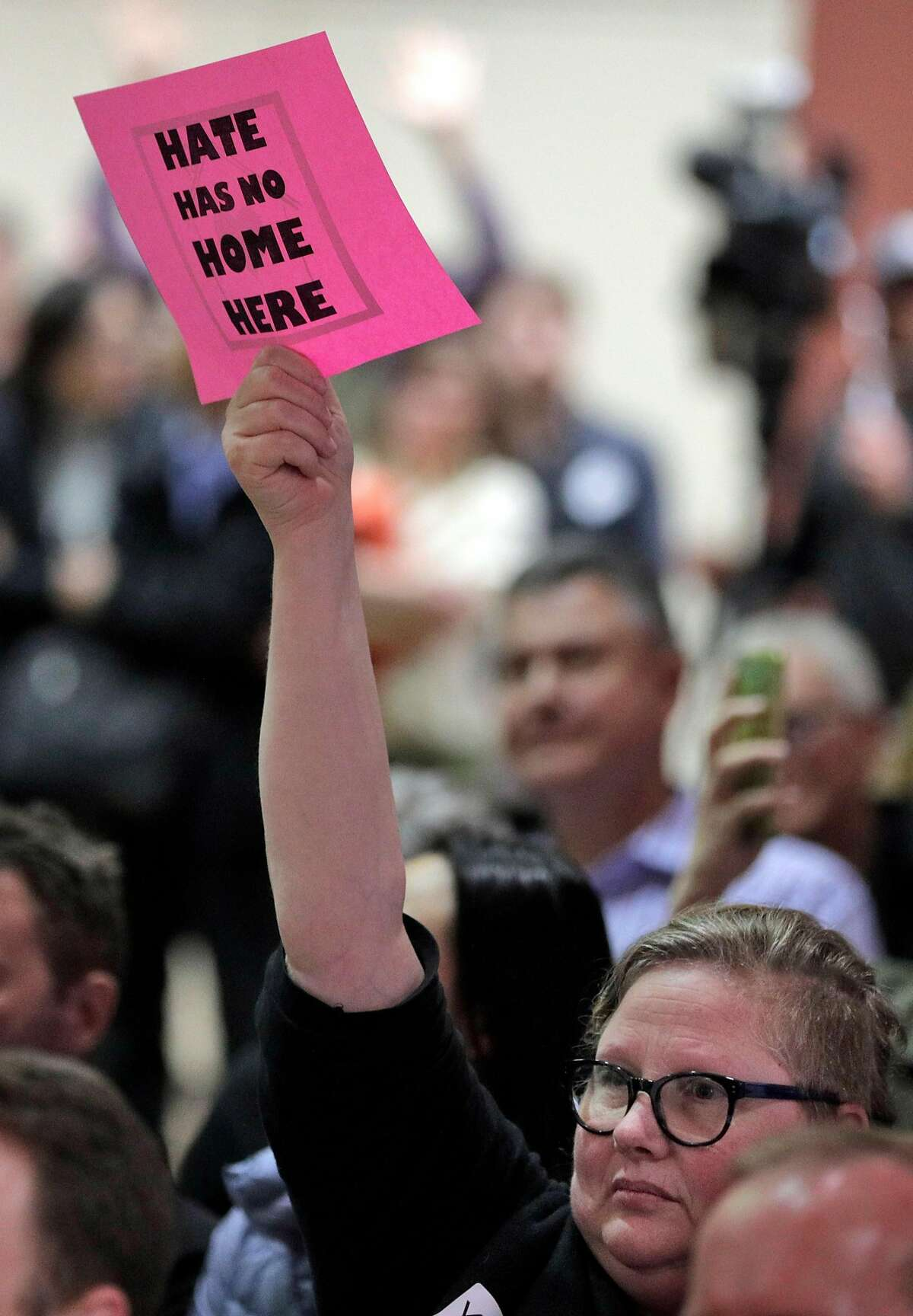 An audience member holds up a sign reading,